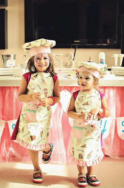 Girls with hat and apron in front of icecream table.